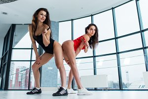 Low angle shot of attractive young women in leotards dancing modern go-go dance teasing with shoulder straps in studio