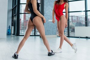 Cropped image of fit sexy female bodies standing in swimsuits and sneakers with focus on buttocks in studio