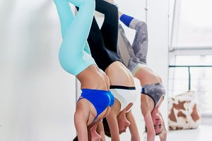 Group of athletic smiling girls standing on hands leaning against wall practicing yoga in fitness studio