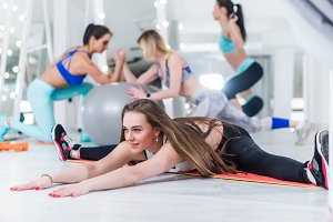 Fit young women working out in gym with smiling young girl in focus doing full split leaning forward