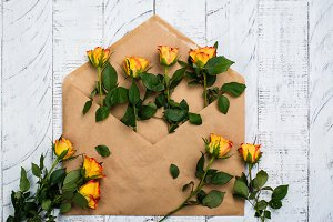 Flat lay composition with craft paper envelope and roses