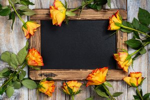 Flat lay composition with roses and blackboard