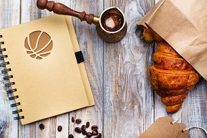 Morning coffee and fresh croissant on wooden table