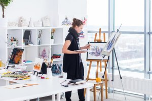 Female painter drawing in art studio using easel. Portrait of a young woman painting with aquarelle paints on white canvas, side view portrait