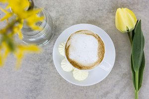 Cappuccino next to yellow flowers