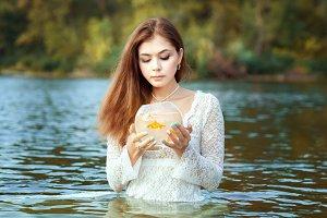 Woman makes a wish gold fish.