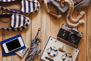 Striped slippers, camera, phone and miniature of the statue of liberty, top view
