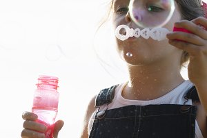A young girl blowing bubbles