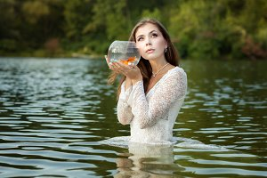 Woman listens to a goldfish.