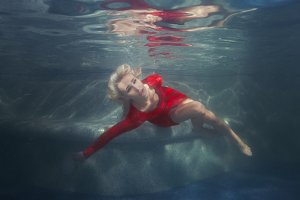 Woman blonde under the water in the pool.