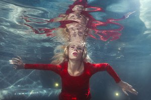 Woman listens to music underwater.