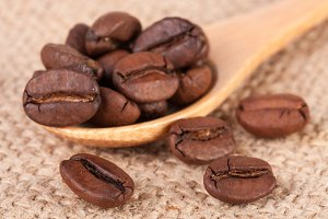 Coffee beans in a wooden spoon on sackcloth