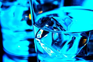 Bar blue glass with ice close up