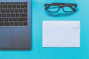 Eyeglasses, envelope and laptop