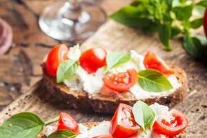 Crostini appetizers with cherry tomatoes, and cheese