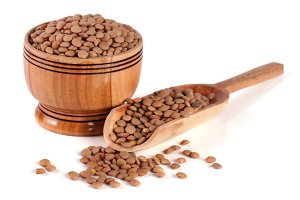 Lentils in a wooden bowl with a scoop isolated on a white background