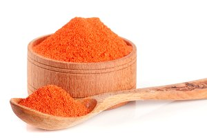 Ground paprika in a wooden bowl with a spoon isolated on a white background