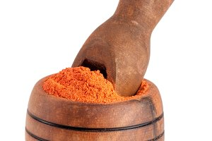 Ground paprika in a wooden bowl with a scoop isolated on a white background