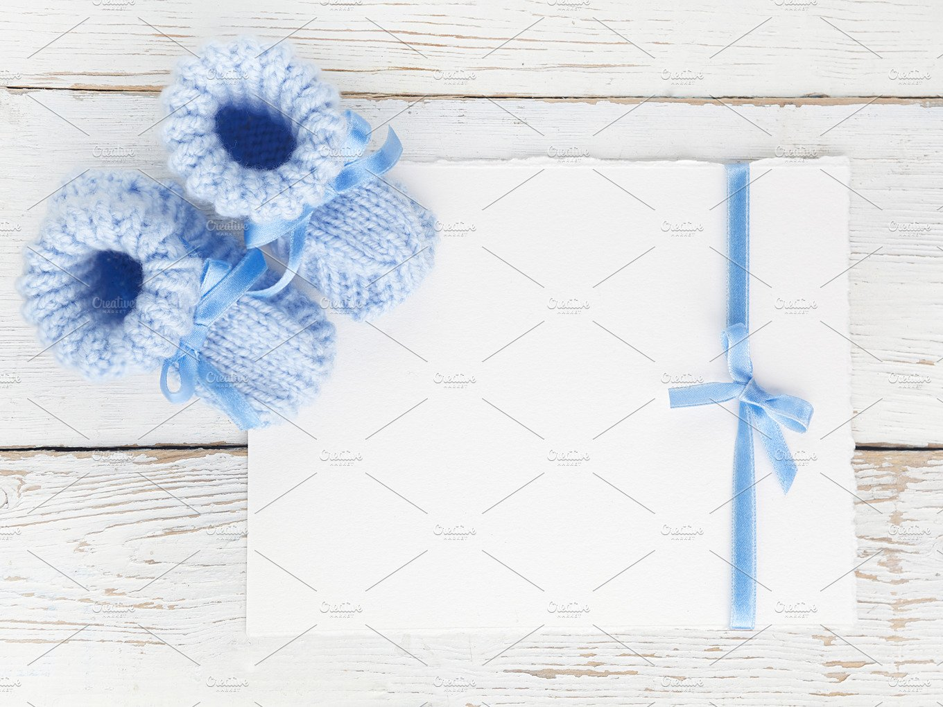 Baby Boy Booties With A Blank Card On A White Wooden