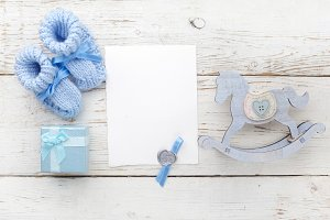 Greeting children form with blue booties, gift and wooden horse. Flat lay