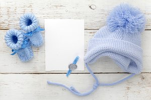 Baby booties with a blank card and cap on a white wooden background. Top view