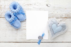 Baby booties with a blank card and heart on a white wooden background. Top view