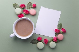 Macaroons, coffee and rose on green background. Top view. Flat lay