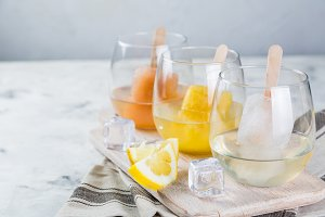 Colorful ice popsicles with wine in glasses