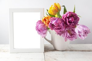 Fresh tulip flowers bouquet and blank photo frame with copy space on wooden background