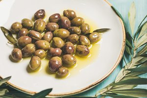 Pickled green olives, olive tree branch, virgin oil, selective focus