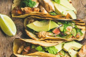 Tacos with grilled chicken, avocado, fresh salsa and limes