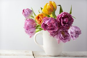 Fresh bouquet of tulips in pot on rustic wood. Vintage stile