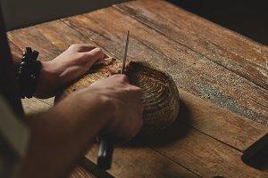 A man baker cuts bread
