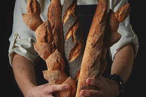 Hands of man holding baguettes