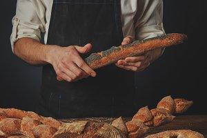 Men's hands hold a baguette