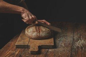 Men's hands cut bread