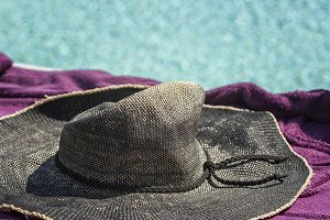 Straw hat on a towel near the pool