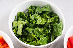Spinach leaves in bowl. Closeup