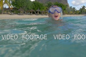 Slow motion view of small boy swimming in the Indian Ocean in the snorkeling mask and take a picture, Port Louis, Mauritius Island