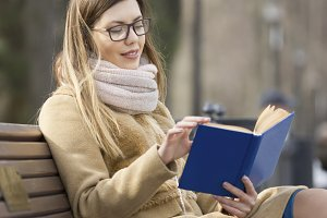 Girl in glasses sitting on a Park bench reading a book
