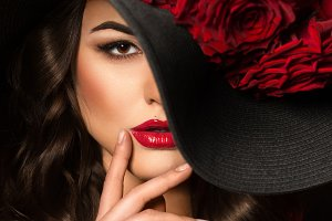 Beautiful woman with red rose in hat