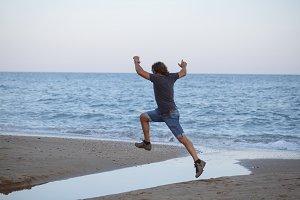 Man jumping on a Mediterranean beach