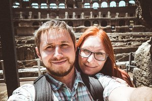 Happy couple doing a selfie on the background of the Colosseum in Rome