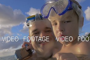 Slow motion view of happy young father with son in the water in snorkeling masks, Port Louis, Mauritius Island