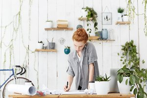 Concentrated young Caucasian redhead woman engineer with hair bun holding pen while creating architectural planning for city district or sketching construction project in modern office interior