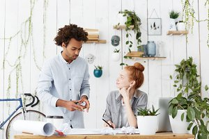 Two young designers working at office: stylish Afro American male sharing ideas on architectural project with his positive ginger woman colleague as they are preparing presentation together