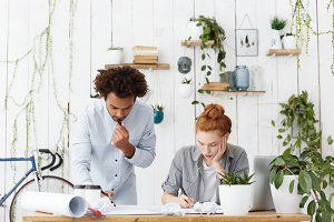 Architecture, engineering and design concept. Confident dark-skinned male and redhead woman architects or engineers brainstorming, drawing blueprint together, both looking busy and concentrated