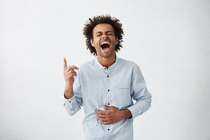 Isolated studio shot of positive cheerful young African American male with funky hair closing his eyes tight and holding stomach, can't stop laughing at good joke while watching comedy show on TV