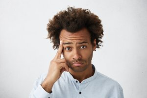 Human emotions, feelings, reaction and attitude. Headshot of African American male holding middle finger inconspicuously at camera, holding hand at his face, teasing haters with that gesture
