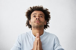 Indoor shot of religious desperate young African American man with tousled hair and stubble pressing palms together in prayer, begging Lord to help his sick wife to recover from serious illness